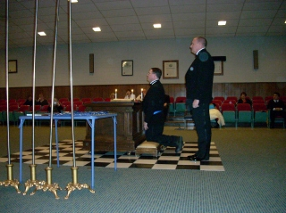 Worshipful Master Mike Clinnin kneels to receive the Charge